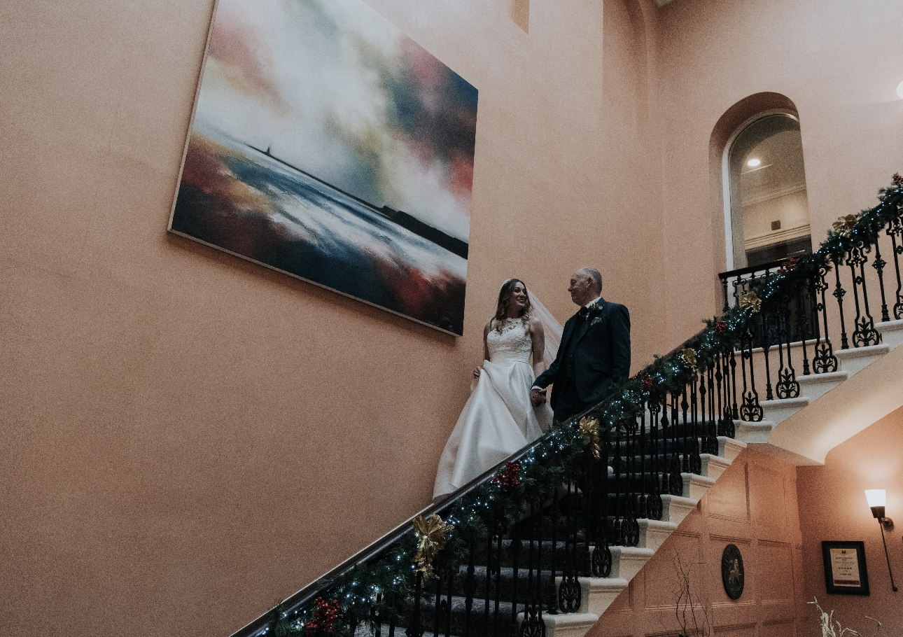 Bride walks down stairs with father
