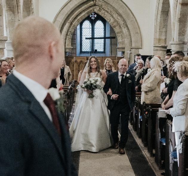 Groom watchs bride walk down the aisle