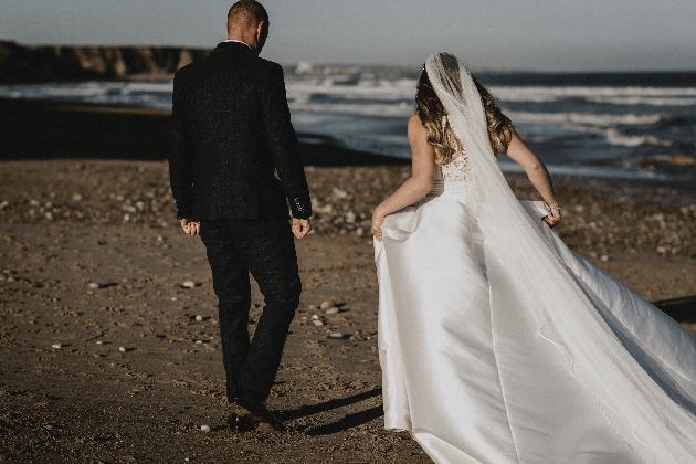 Couple walk along beach