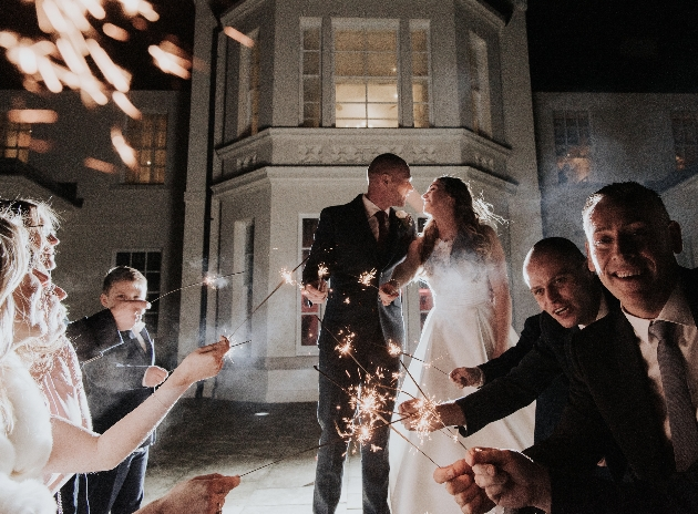 Wedding party outside venue with sparklers