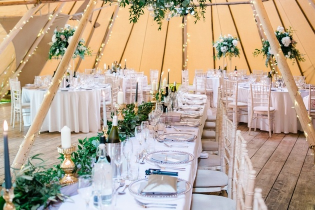 Inside the tipi at Brinkburn with white tables dressed with flowers