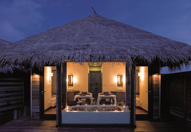 spa beds in room lit at night by candles