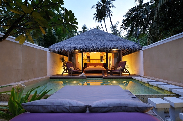 lounge bed by pool at night with view of hut lit up
